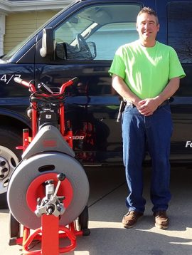 Mark Ripp standing along side a sewer and drain cleaning machine
